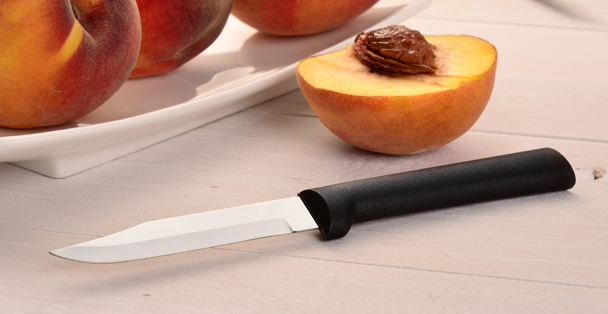 Black handled Regular Paring Knife by a cut peach.