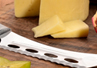 Cheese knife on a cutting board with star fruit and a block of cheese.