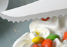 A close up of the serrated slicer cutting an ice cream cake.