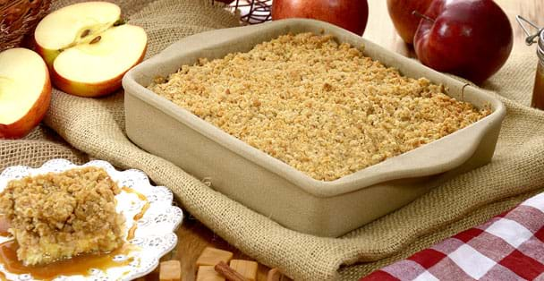 The square baker with a apple cobbler and apples.