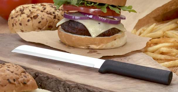 "The black handled serrated 6"" bread slicer laying by a hamburger."