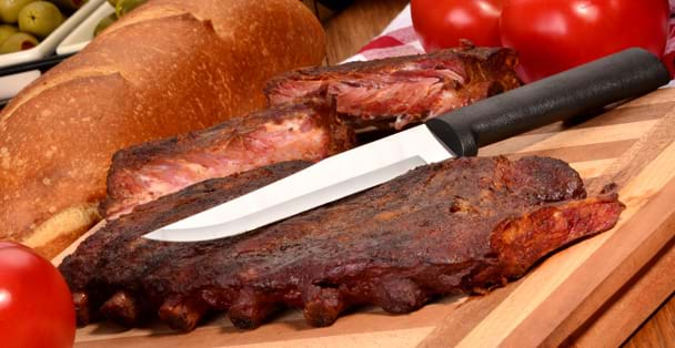 Black handled Stubby Butcher slicing ribs.