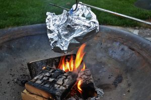 Popcorn is cooked in foil over the heat of a campfire.