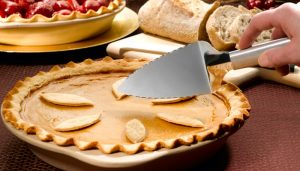 A pumpkin pie with a Rada Serrated Pie Server.