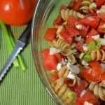 A bowl of pasta salad alongside a Rada Tomato Slicer.
