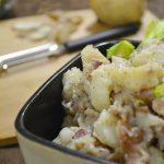 A bowl of German potato salad alongside a Rada Vegetable Peeler.