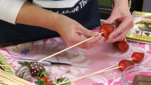 placing a strawberry onto a bamboo skewer
