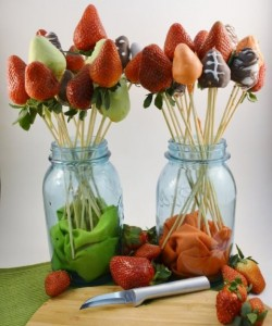 Strawberries dipped in chocolate and on a bamboo skewer.