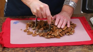 pecans on a cutting board being chopped