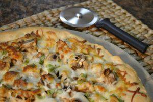 A delicious Chicken Alfredo Pizza with a Rada Pizza Cutter.