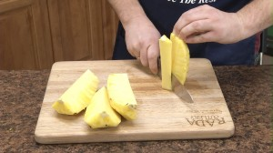 slicing the pineapple up to remove the core