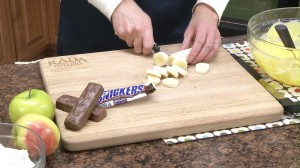 A banana is chopped in preparation of a scrumptious Snickers Salad.