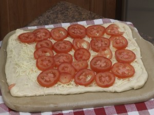 Pizza dough with tomatoes on top of mozzarella