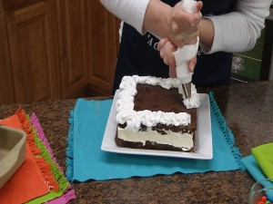 Whipped topping being poured on Giant Brownie Ice Cream Sandwich