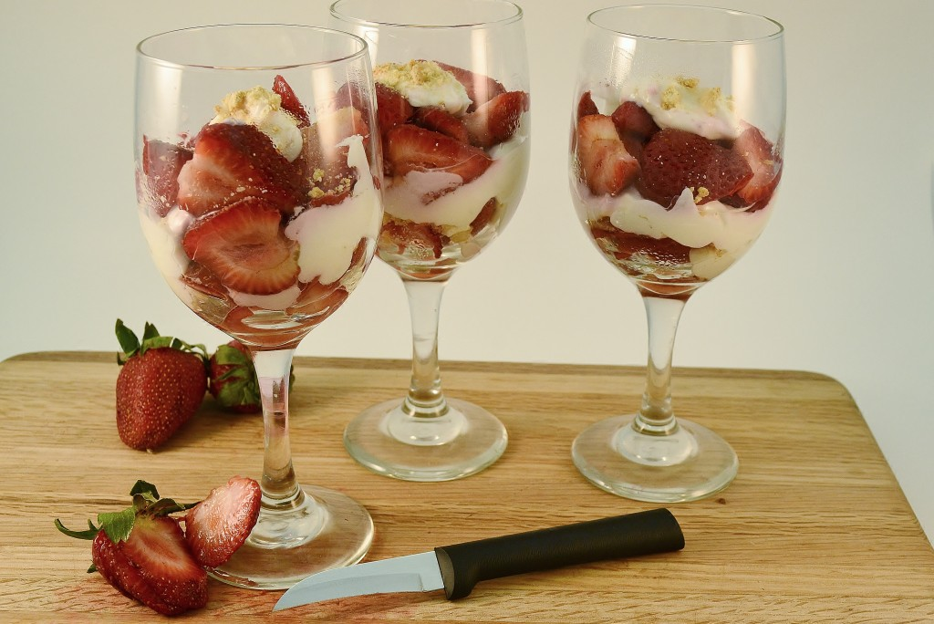 A Rada Granny Paring knife sits in front of three strawberry cheesecake parfaits.