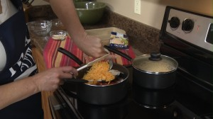 Adding Cheddar Jack cheese to saucepan