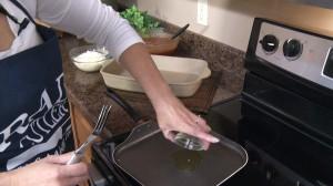 Placing olive oil on skillet