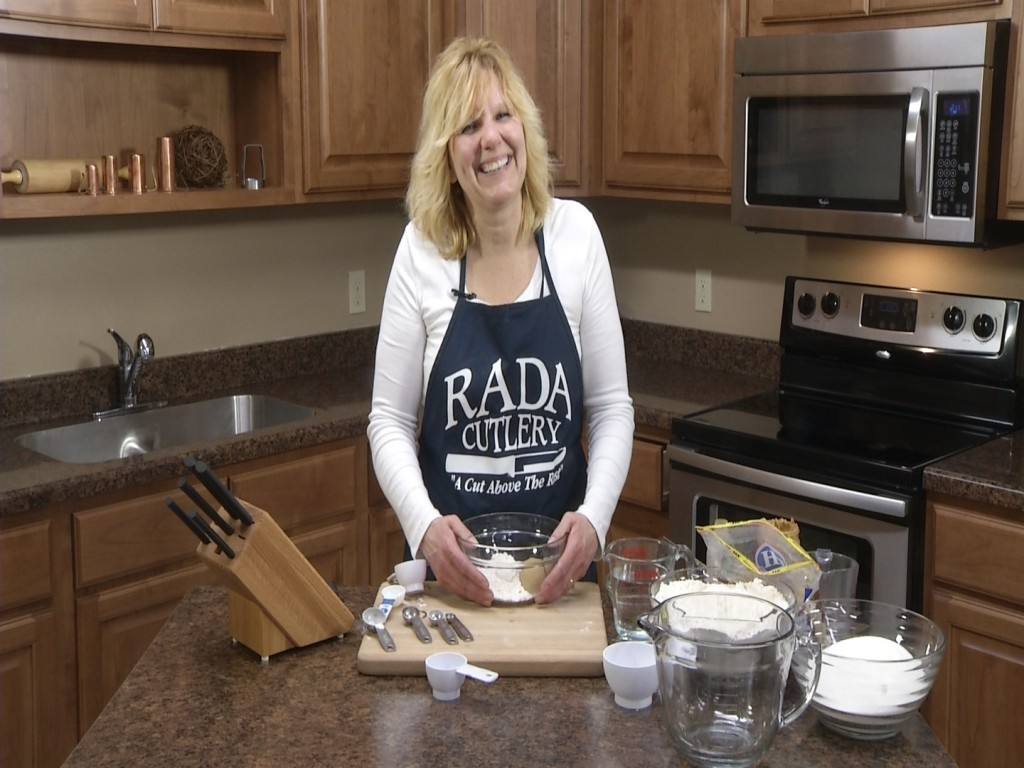 Kristi poses with ingredients and superior Rada Cutlery products.