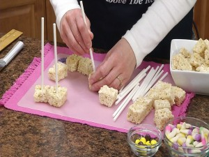Placing cookie sticks in Rice Krispie Treats.