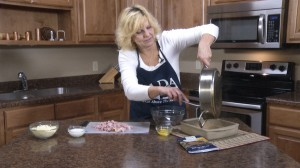 Kristy placing ingredients in pan.
