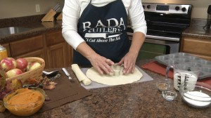 Kristy cutting pie crusts with cookie cutter.