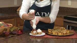Adding whipped cream to completed pumpkin pies