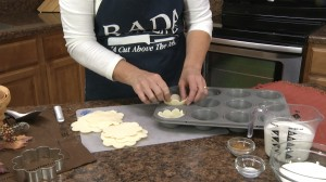 Kristy placing pie crusts in muffin tins.