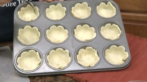 Muffin tin with pie crusts.