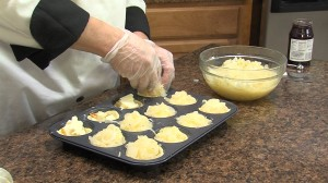 Adding onions to muffin tins