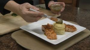 Adding pesto to salmon dish.