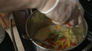 Adding vegetables to risotto pot.