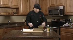 Chef Ted pours sauce on cod.