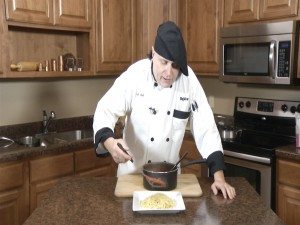 Chef Ted pours marinara sauce over angel hair pasta.