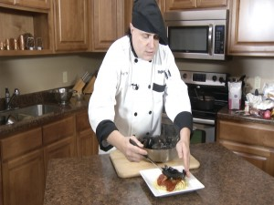 Chef Ted places mussels over pasta with marinara.