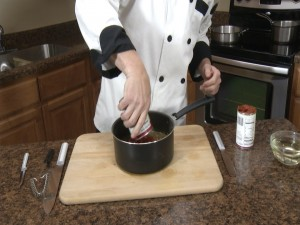 Chef Ted adds a can of tomato paste to his pan.