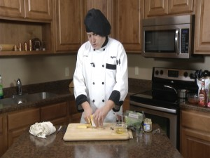 Chef Ted slices cheese.