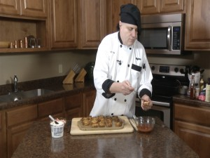 Chef Ted adding cocktail sauce to toast.