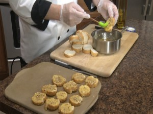 Chef Ted coats bread slices with brush.