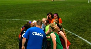 Soccer team in gesture of unity.