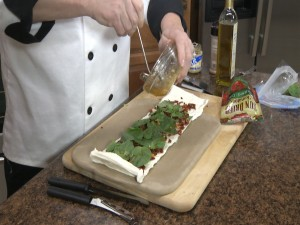 Chef Ted adds olive oil to basil.