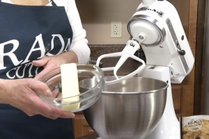 Kristy adds butter to mixer.