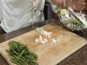 Chef Ted adds sweet onion to bowl filled with asparagus.