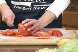Kristy cuts tomatoes with the Rada Tomato Slicer.