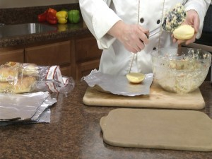 Chef Ted places the chicken and Swiss mixture on a Dutch potato bun.