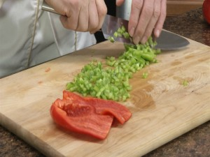 Chef Ted chops and dices a green bell pepper.