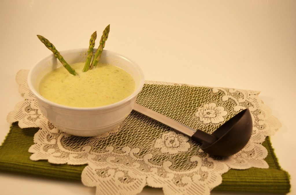 A bowl of asparagus soup with a Rada Non-Scratch Spoon.