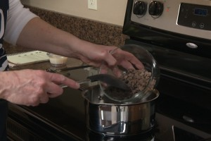 Kristy adds semi-sweet chocolate chips to a saucepan on low heat.