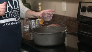 Kristy adds vegetable oil to pan.