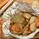 A tasty hobo dinner made in foil including beef and vegetables. Pictured beside it is the Rada Vegetable Peeler.
