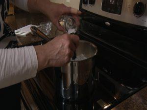 Kristy heats and mixes ingredients in medium saucepan.